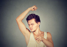 Man smelling armpit stinks bad odor pointing finger at camera. Closeup portrait of young man, smelling, sniffing his armpit, something stinks, bad, foul odor stock photo