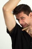 Man smelling badly under he's armpits. And pointing there with his finger Royalty Free Stock Photo