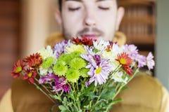 Man smelling chrysanthemums flowers Royalty Free Stock Photo