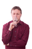 Man is smelling at a glas of grappa Stock Photo