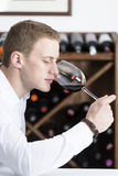 Man smelling a glass of red wine. Young man on a wine tasting session on the olfactory phase is analyzing the wine with the wine glass in the nose Stock Photo