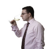 Man smelling a glass of white wine. Portrait of a man with tie smelling a glass of white wine Royalty Free Stock Photos