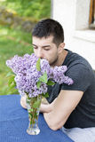 Man smelling lilac  flowers Stock Photo