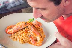 Man Smelling Prawn and Pasta Dish on White Ceramic Plate Stock Photography