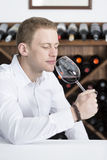 Man smelling a red wineglass. Young man on a wine tasting session on the olfactory phase is analyzing the wine smelling the wineglass at a restaurant Stock Photo