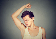 Man, smelling, sniffing his armpit, something stinks bad, foul odor. Closeup portrait of young man, smelling, sniffing his armpit, something stinks, very bad Royalty Free Stock Image