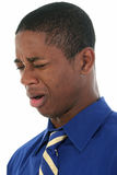 Man Smelling Something Awful. Close up headshot of African American man cringing from bad smell.  Wearing blue shirt and blue and yellow tie Royalty Free Stock Photography
