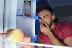 Man smelling stinky stale cheese. In refrigerator stock images