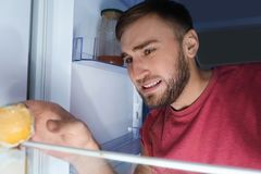 Man smelling stinky stale cheese. In refrigerator stock photography