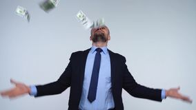 Man is smelling, throws and enjoys the falling dollar bills stock footage