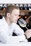 Man smelling a white wineglass. Young man on a wine tasting session on the olfactory phase is analyzing the white wine smelling the wineglass at a restaurant Royalty Free Stock Photo