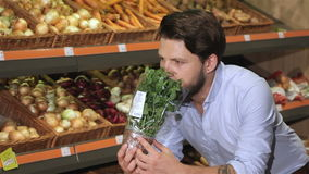 Man smells basil at the supermarket stock video footage