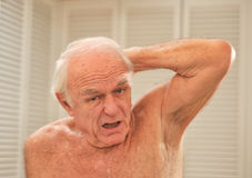 Man smells his arm pit and reacts Royalty Free Stock Photography