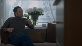 Man smells a rose and dreaming about his wife in the living room royalty free stock photo