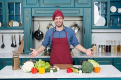 Man smile in chef hat in kitchen. Happy cook at table. Vegetables and tools ready for cooking dishes. Food preparation and cooking. Recipes. Vegetarian menu and Royalty Free Stock Photo