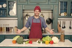 Man smile in chef hat in kitchen. Happy cook at table. Vegetables and tools ready for cooking dishes. Food preparation. And cooking recipes. Vegetarian menu and royalty free stock photography
