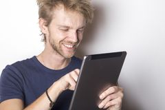 Happy young man using his mobile tablet stock photo