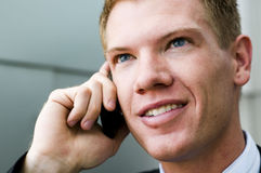 Man with smile talking on cell phone Stock Images