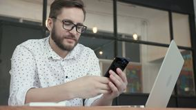 Man smile and using phone for chatting in office stock footage