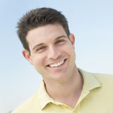 Man Smiling Against Clear Blue Sky Stock Photo