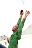 Man smiling with arms raised and mobile phone Stock Photos