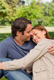 Man smiling as his friend rests her head on his shoulders Stock Photos
