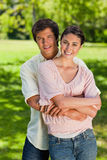 Man smiling as his he holds onto his friends waist Stock Images