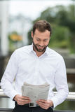 Man smiling as he reads the newspaper outdoors Royalty Free Stock Image
