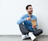 Man smiling with asian food and chopsticks. Portrait of a young man smiling with asian food and chopsticks royalty free stock photography