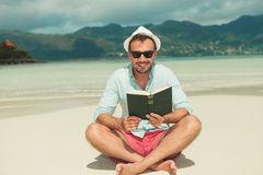 Man smiling and on the beach enjoying reading a green book Royalty Free Stock Image