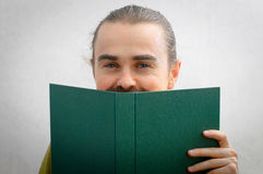 Man smiling from behind the book stock photos
