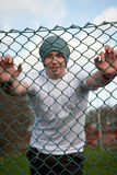 Man smiling behind fence 2. A young man smiling behind a fence Royalty Free Stock Photos