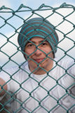 Man smiling behind fence 3. A young man smiling behind a fence Stock Photos