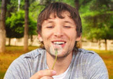 Man smiling and blowing Dandelion Royalty Free Stock Photos