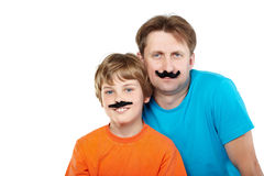 Man and smiling boy with glued artificial mustache Stock Image