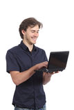 Man smiling browsing internet on the laptop Royalty Free Stock Photo