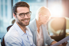 Man smiling at camera while his colleague reading document Royalty Free Stock Photography