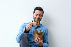 Man smiling with chopsticks and noodles Royalty Free Stock Photos