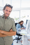 Man smiling in creative office with arms folded Stock Image