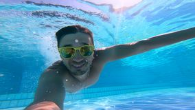 A man is smiling while diving underwater. 4K stock video footage