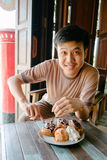 Man smiling eating waffle with ice-cream at vintage cafe Stock Photos