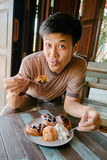 Man smiling eating waffle with ice-cream at vintage cafe Royalty Free Stock Images