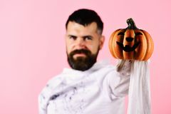 Man with smiling face expression on pink background, defocused. Halloween and happy holiday concept. Guy with beard holds jack o lantern with smile, close up royalty free stock images