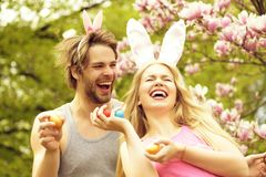 Man and smiling girl with bunny ears holding eggs stock photo