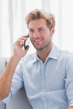 Man smiling while he is having a phone conversation. On the couch Stock Photos