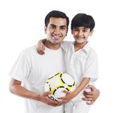 Man smiling with his son. Portrait of a men smiling with his son and holding a soccer ball Royalty Free Stock Photo