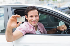 Man smiling and holding his driving license Royalty Free Stock Image