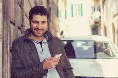 Man smiling holding a mobile phone standing outdoors next to his car. Man smiling holding a mobile phone standing outdoors next to his new car texting Stock Image