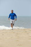 Man smiling and jogging at the beach Royalty Free Stock Image