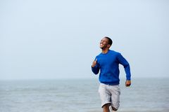 Man smiling and jogging outdoors Stock Photo